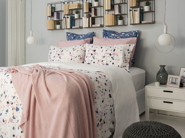 king size bed in a grey painted bedroom with statement gold brass lighting at the bedside by bhs spring summer 2018