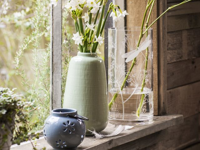 rustic, natural vases with spring flowers on a windowsill in a wood clad house from Tesco's willow ss18 homeware trend collection