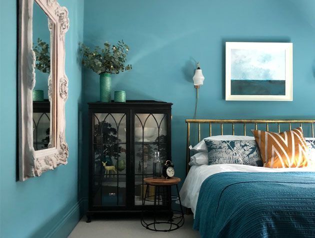 teal scheme bedroom with teal walls teal bedding and vintage furniture with gold and orange accents