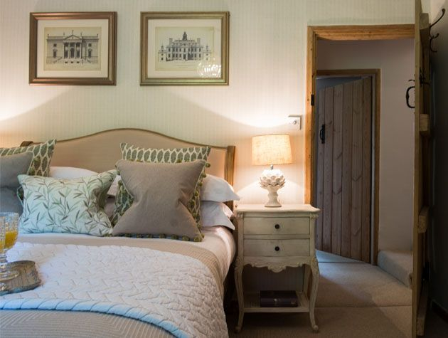 bedroom with neutral decor grey beddring vintage bedside table and vintage wall art