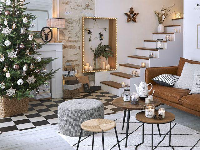 Living room with Christmas tree, festive decor, a brown sofa and grey layered rugs -maisons-du-monde-living-room-goodhomesmagazine.com