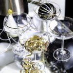 cocktail glasses on a glass bar cart with party accessories at the Ideal Home Show Good Homes roomset
