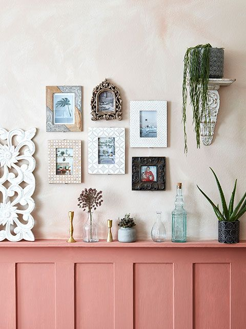 Half panelled wall painted a dusky coral, which has then been used as a shelf to display vases and plants