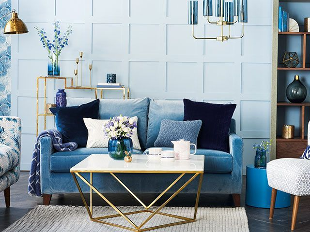Blue panelling with velvet blue sofa, brass accents and shades of blue cushions