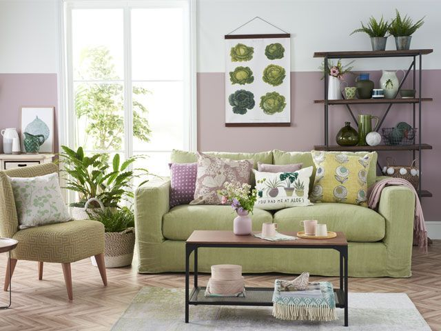 Green sofa in a living room with purple painted and botanical home accessories living-room-goodhomesmagazine.com