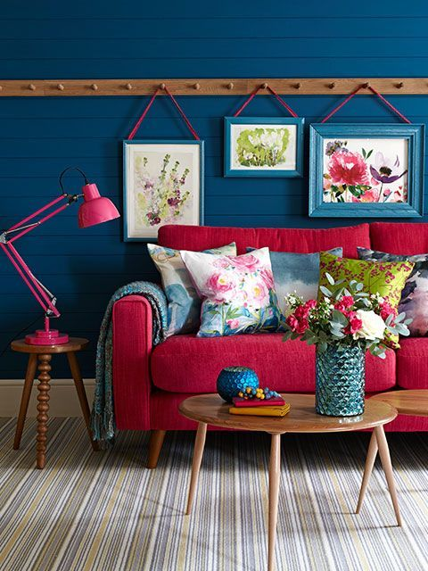Bright, pink sofa with painterly pink and blue cushions, against a blue panelled wall with peg rail and hanging pictures