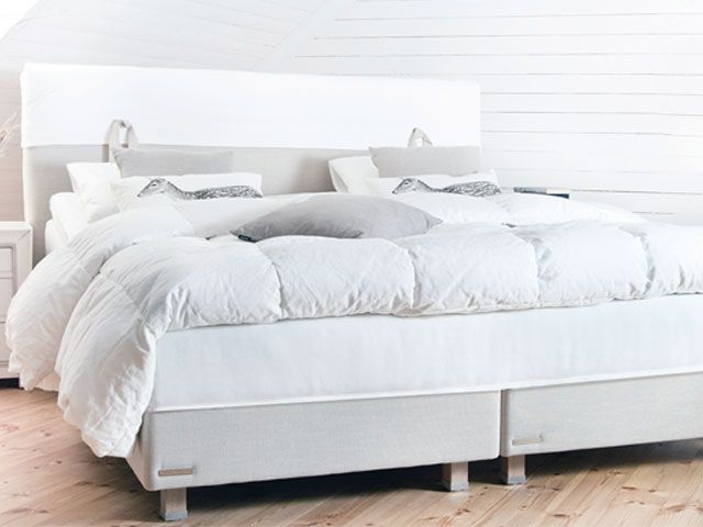 A white mattress is placed on top of a grey bed frame and dressed with a white duvet -unikbed-bedrooms-goodhomesmagazine.com