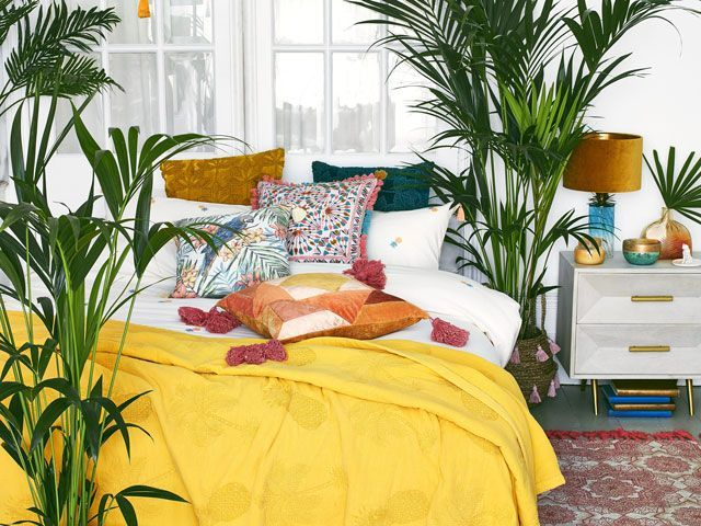 a selection of cushions on a bed in a bright bedroom focussing on the maximalism trend from Debenhams Matthew Williamson ss19 collection