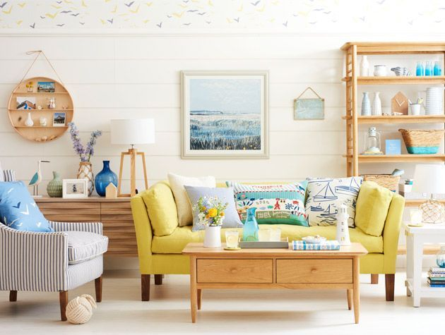 nautical themed living room with yellow sofa white wood walls - goodhomesmagazine.com