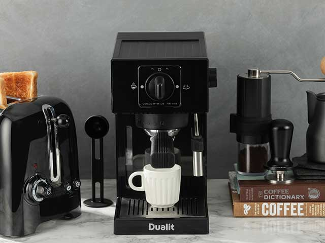 Dualit coffee machines nxt to toaster and coffee dictionary on marble background