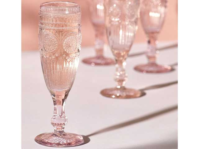 next embossed champagne flutes on a table with pink background