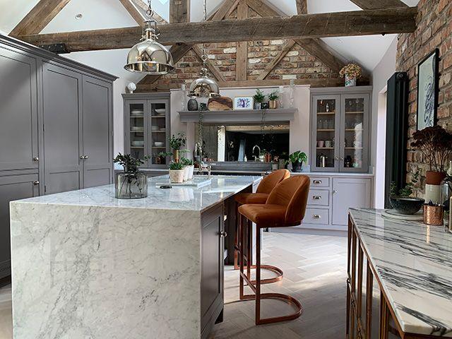Barn style kitchen with marble kitchen island and orange bar stools - news - goodhomesmagazine.com