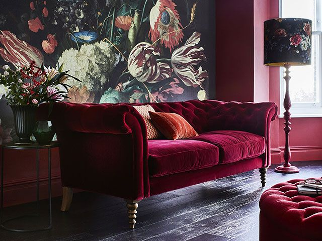 red living room with velvet sofa and wall mural - goodhomesmagazine.com