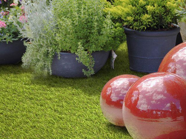 Lovage Green artificial grass rug seller in a garden - goodhomesmagazine.com