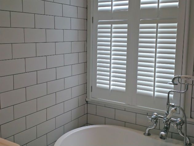bathroom with tiled wall bath and shutters