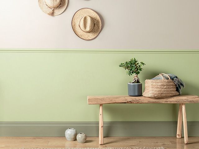 green painted wall in hallway with hats on the wall - news - goodhomesmagazine.com