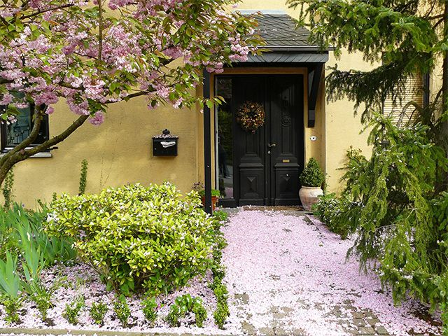 pretty front exterior of house - these outdoor plants will help you sell your house - inspiration - goodhomesmagazine.com
