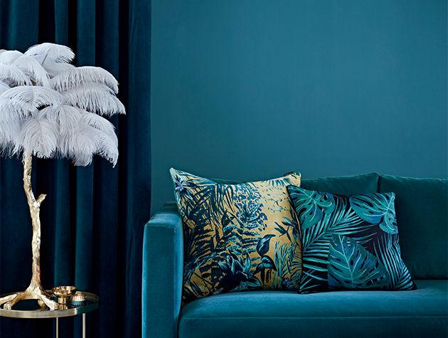 blue sofa with cushions blue wall and curtains