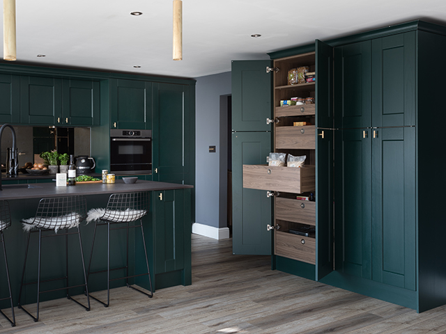kitchen with dark green cabinets, chairs and pull out drawers