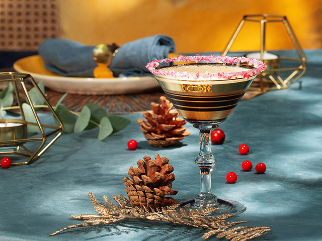 A martini glass filled with GREY GOOSE® Candy Cane Lane cocktail, and garnished with crushed candy canes