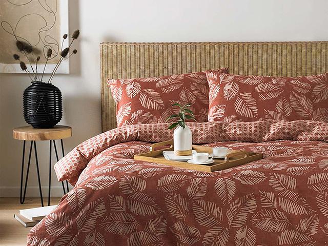 red japanese inspired bedding on wicker bed - japandi interiors trend - goodhomesmagazine.com