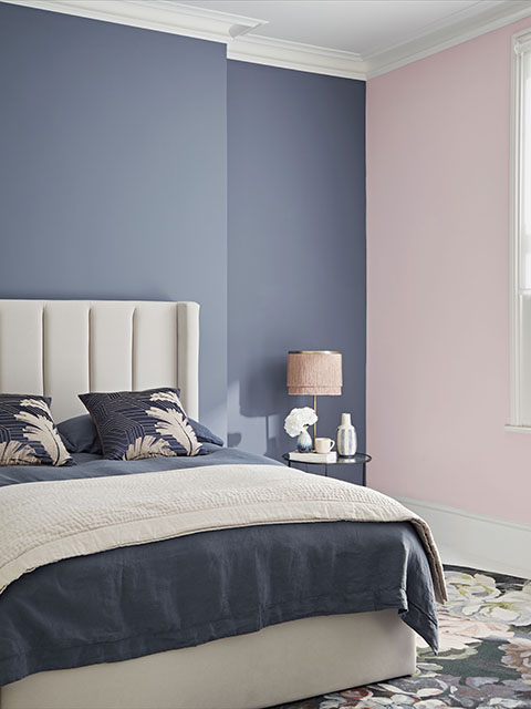 Bedroom with grey and pink walls, double bed and night stand with pink lamp, Crown Paint Good Homes Approved