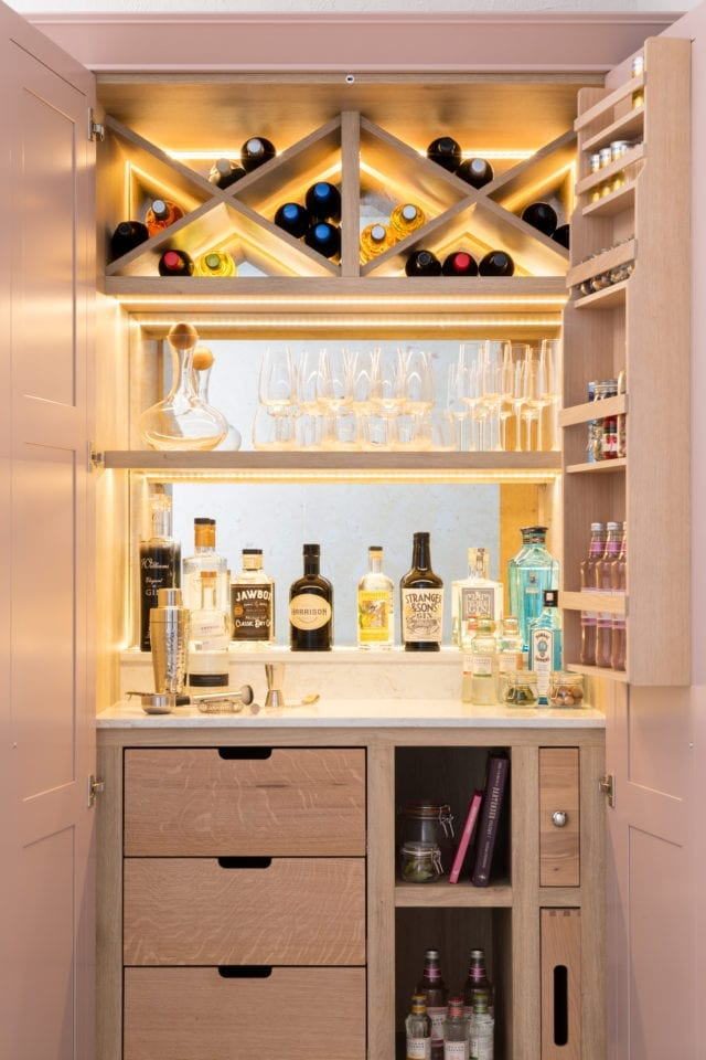 drinks cabinet with glasses, gin and wine bottles