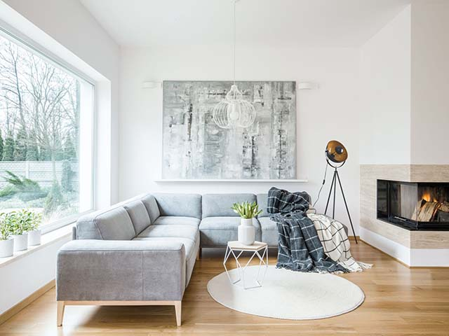 White rug next to grey corner couch in living room interior with fireplace and painting