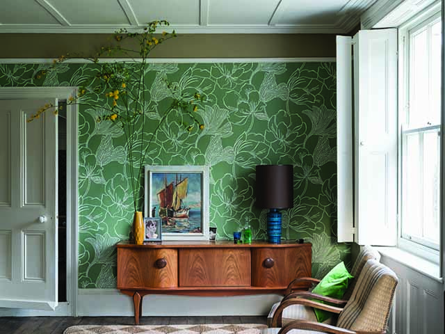 Green wallpaper feature wall in lounge with framed print and oak furniture, goodhomesmagazine.com