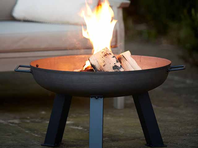 A firepit on legs on a garden patio in front of garden furniture