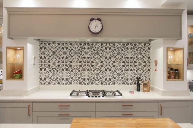 kitchen hob with gas burner and patterned tiled splashback