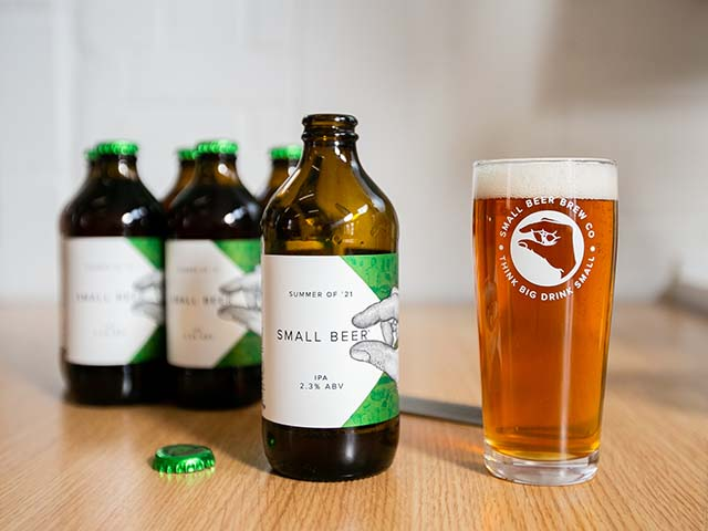small beer bottles with full pint glass on wooden surface, Goodhomesmagazine.com