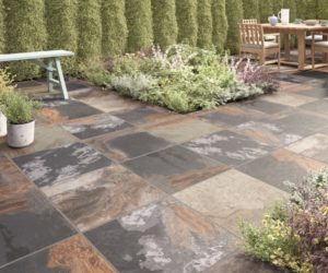 traditional garden paved with rustic outdoor tiles, hedging, planted beds and wooden dining table