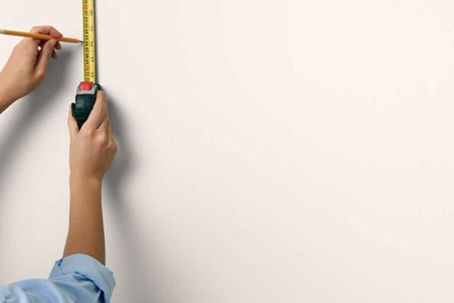 Woman's hand markign a spot on a wall with a pencil and a measuring tape - Painted headboard - Goodhomesmagazine.com
