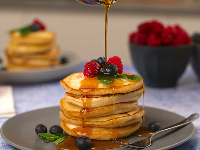 A stack of fluffy American pancakes topped with berries and maple syrup that is being poured - Father's Day breakfasts - Goodhomesmagazine.com