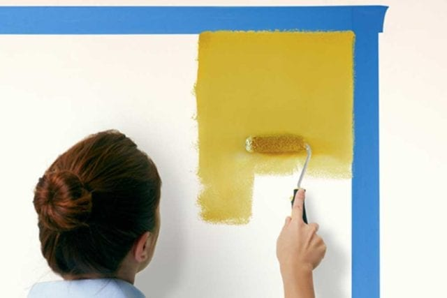 Woman using a roller brush and yellow paint to paint an area on the wall that has been marked out with masking tape - Painted headboard - Goodhomesmagazine.com