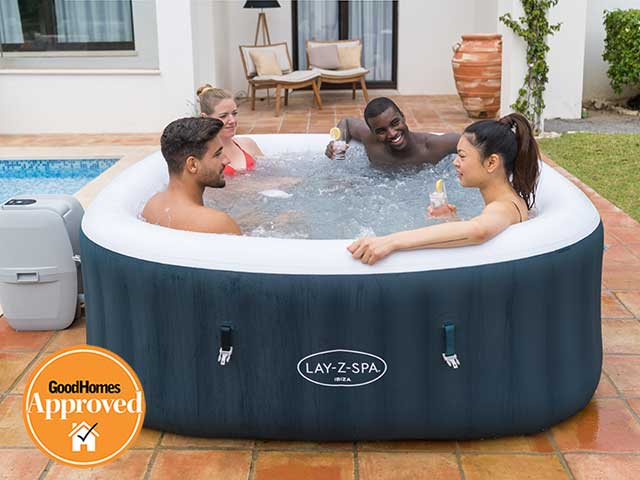 Lay-Z Spa with four people in next to swimming pool, goodhomesmagazine.com