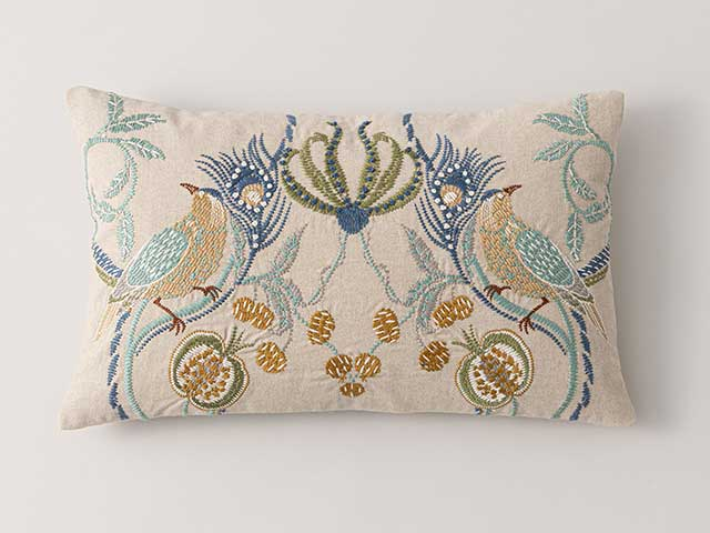 A cream cushion with an embroidered animal pattern - Goodhomesmagazine.com