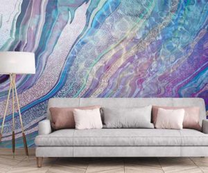 Lilac and blue swirling wallpaper in living room with grey sofa and lamp - Goodhomesmagazine.com