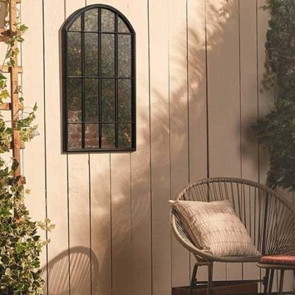 Rattan chair and plant trellis in front of a white panelled fence that has an arched mirror hanging on it - Garden mirrors - Goodhomesmagazine.com