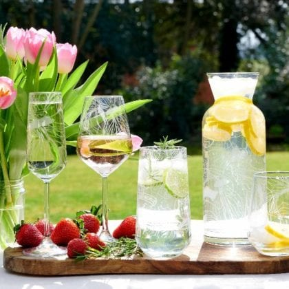 Wooden tray on a table in a summer garden with a selection of RHS glassware including champagne flute, wine glass, hi ball and carafe etched with iris design