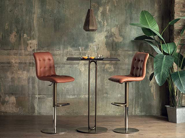 Two brown leather stools with dark brass frames and a tall brass table - Earthy tones - Goodhomesmagazine.com