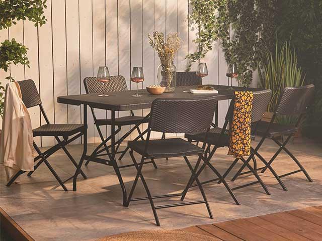 A garden with a large black table and six chairs in rattan style on the patio - 2021 garden furniture - Goodhomesmagazine.com