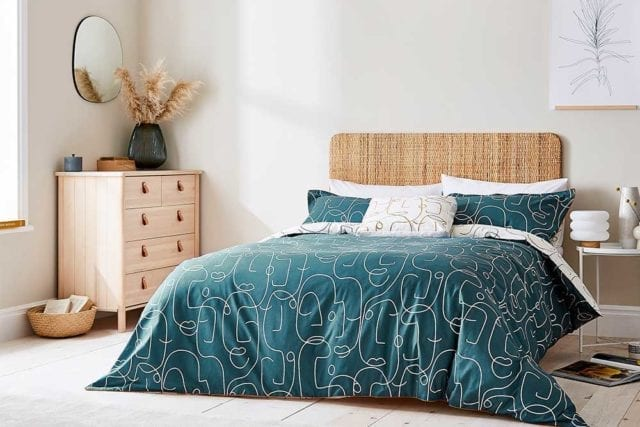 A bedroom with a woven wooden headboard and a teal bedding set with a single line continuous pattern of abstract faces - Bold bedding - Goodhomesmagazine.com