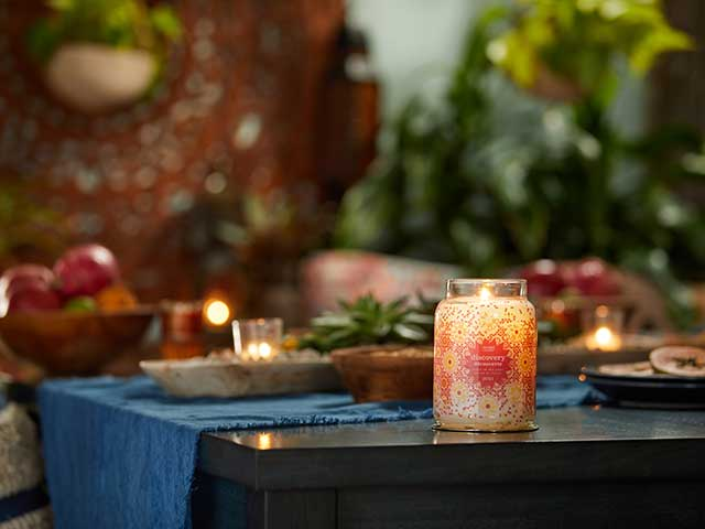 Yankee candle with candles in background on outdoor table with blue runner
