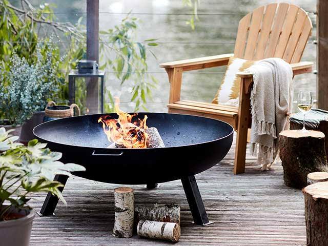 Outdoor open firepit on balcony with wooden chair nearby, goodhomesmagazine.com