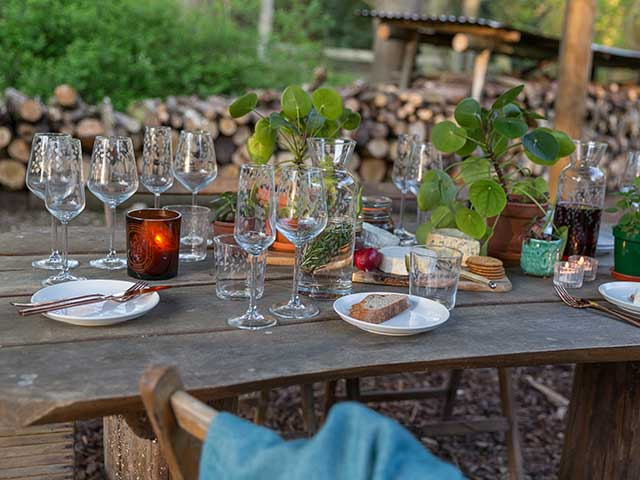 Wine glasses and food on distressed wooden table in outdoor setting, goodhomesmagazine.com