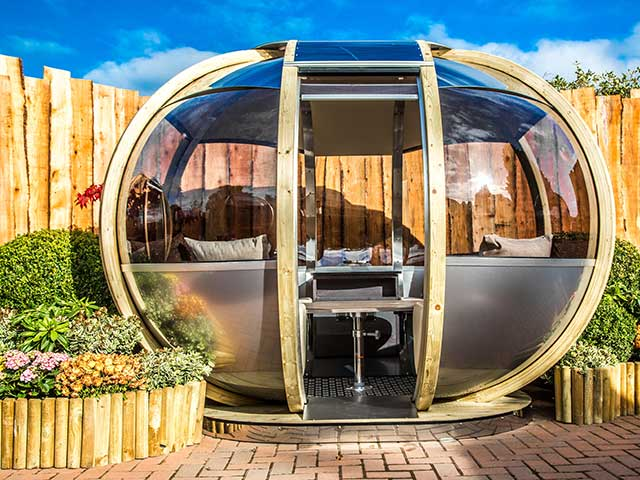 small glass garden pod surrounded by a floral bed