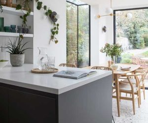 Open plan kitchen in this Melbourne inspired home with dark units and white worktops and dining table in background with floor length windows