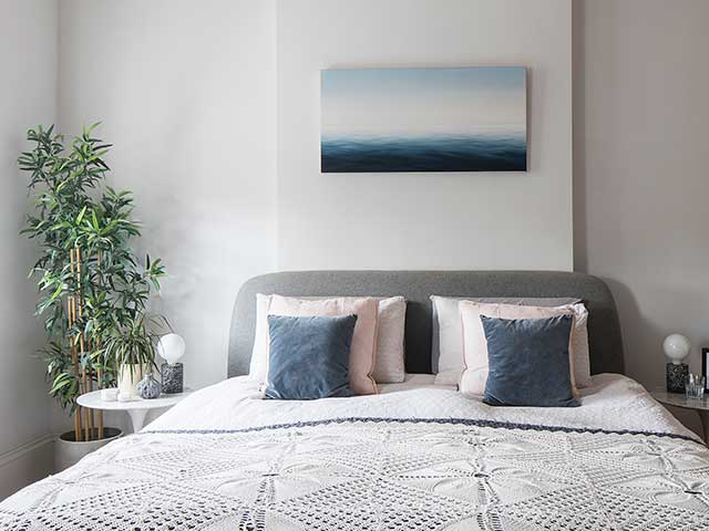 Master bedroom in neutral colours with geometric duvet and green plant